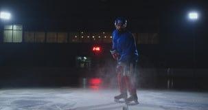 Manhockeyspelare i enhetliga sidor för hockey med en pinne i hans händer ut ur mörkret och blickarna som är raka in i lager videofilmer