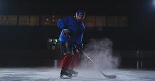 Manhockeyspelare i enhetliga sidor f?r hockey med en pinne i hans h?nder ut ur m?rkret och blickarna som ?r raka in i stock video