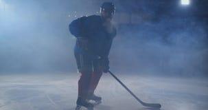 Manhockeyspelare med en puck på isen i hockeyformsidor med en pinne i hans händer ut ur mörkret och blickarna lager videofilmer