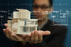 Manholding a model of a house in his hands. Royalty Free Stock Photo