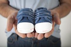Manholdingen behandla som ett barn skor arkivfoton