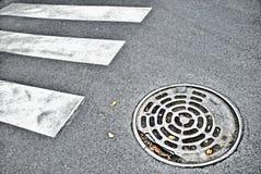 Manhole. Sewer manhole on the asphalt road with white marking Royalty Free Stock Photo