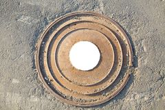 Manhole cast iron heavy brown with a pattern of several rings on the background of concrete screed. In the center of the round whi royalty free stock photo