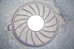 Manhole cast iron heavy lilac with a pattern of divergent rays on the background of gray asphalt. In the center of the round white royalty free stock photography