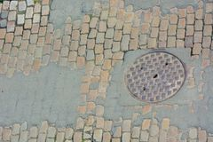 Manhole in a cobbled old street. Manhole in a cobbled old street in Antwerp , you still see the old horse trails Stock Photography