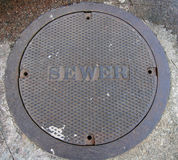 Manhole Cover. In a city sidewalk stock photography