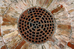 Manhole cover. In an ancient courtyard Royalty Free Stock Photos
