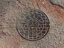 Manhole cover for access to gas mains. Manhole cover allowing access the gas mains and stop valve of Southern California Gas company in dirt road Royalty Free Stock Photo