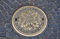Manhole cover in brass Stock Image