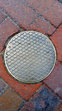 Manhole Cover on a Brick Road. Manhole cover on an old red brick road Stock Photo