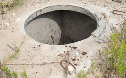 Manhole without cover in the concrete block Stock Photo