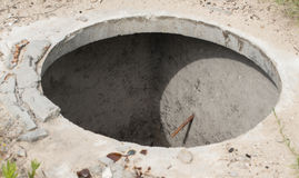Manhole without cover in the concrete block Royalty Free Stock Photo