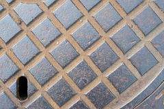 Manhole cover with hole and rust Royalty Free Stock Photos