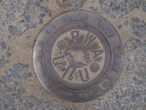 Manhole cover on pavement with patterns royalty free stock images