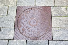 Manhole cover and pavement paving made of natural stone Royalty Free Stock Image