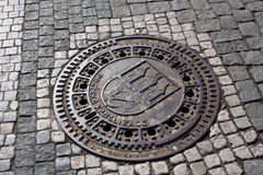 Manhole cover on pavement Royalty Free Stock Image