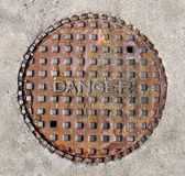 Manhole cover saying danger isolated Stock Photos