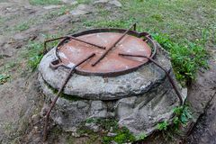 Manhole cover secured with four bended and welded onto cover reinforcing bars. Closeup of a manhole cover secured with four bended and welded onto cover royalty free stock photography