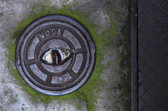 Manhole cover. Small manhole cover on a damp concrete floor royalty free stock photo