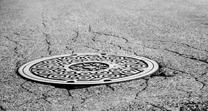Manhole Cover. A manhole cover in the street surrounded by cracked pavement royalty free stock images