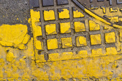 Manhole cover yellow. Detail of a sewer cover in the street, painted yellow royalty free stock photo