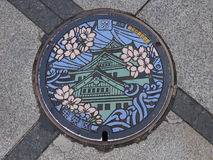 Manhole drain cover on the street at Osaka, Japan Stock Photos