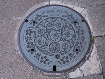 Manhole drain cover on the street at Osaka, Japan Royalty Free Stock Photos