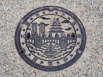 Manhole drain cover on the street at Osaka, Japan royalty free stock image