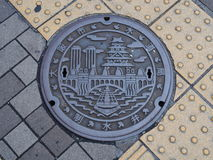 Manhole drain cover on the street at Osaka, Japan royalty free stock images