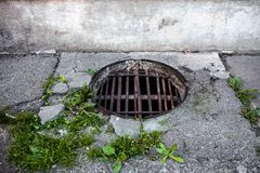 Manhole with the handmade metal armature cover Royalty Free Stock Photo