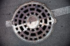 Manhole with metal cover in asphalt with white road marking line Royalty Free Stock Photos