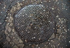 Manhole with metal cover in the cracked asphalt surface Stock Images