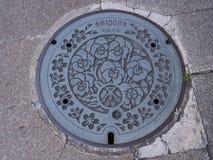 Manhole odcieku pokrywa na ulicie przy Osaka, Japonia Zdjęcia Royalty Free