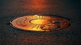 Manhole pokrywa w zmierzchu Obraz Stock