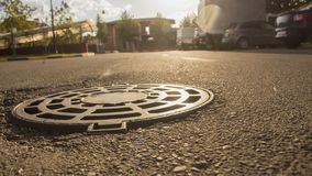 The manhole on the road glitters in the evening sun stock photo