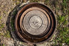 Manhole with rusty metal cover and water in its grooves Stock Photo