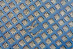Manhole. Texture consisting of a portion of the manhole interspersed with small stones and sand Stock Photography