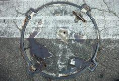 Manhole z metal pokrywą z zebry ocechowania linii na nim skrzyżowaniem Obraz Stock