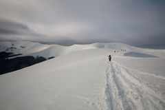 Manière au sommet d'arête neigeuse de montagne avec la hausse de touristes Photos stock