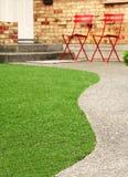 Manière de promenade avec l'herbe parfaite aménageant en parc avec l'herbe artificielle dans la zone résidentielle Image libre de droits
