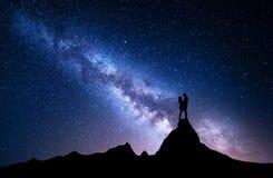 Manière laiteuse avec la silhouette des personnes Horizontal de nuit Image stock