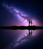 Manière laiteuse avec la silhouette des personnes Paysage avec le ciel nocturne Image libre de droits