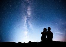 Manière laiteuse avec la silhouette des personnes Paysage avec le ciel étoilé de nuit Homme et femme debout sur la montagne avec  Image stock