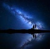Manière laiteuse Ciel étoilé de nuit avec des silhouettes d'un couple Photos stock