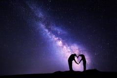 Manière laiteuse Homme et femme tenant des mains dans la forme de coeur Photographie stock