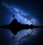 Manière laiteuse Silhouette d'un homme heureux sur la roche Photographie stock libre de droits