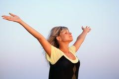 Mani alzate bella donna verso l'alto contro il cielo Fotografie Stock Libere da Diritti