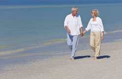 Mani ambulanti della holding delle coppie maggiori felici sulla spiaggia Fotografia Stock