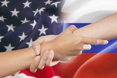 Mani amiche con le bandiere americane e russe Immagini Stock Libere da Diritti