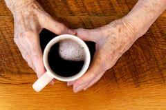 Mani & tazza di caffè artritiche Fotografia Stock Libera da Diritti